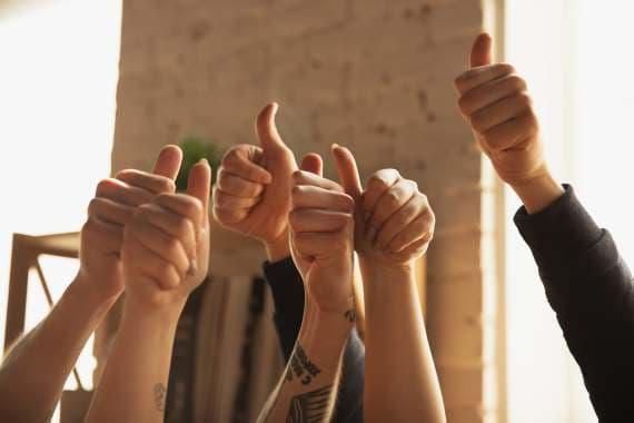 En flot hænder holdt i vejret med tommefingeren opad