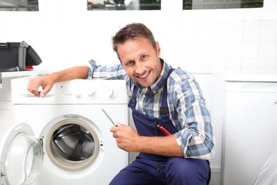 Smilende håndværker ved vaskemaskine.