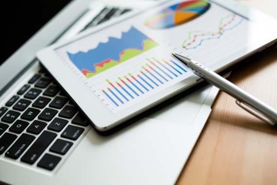 Tablet med illustration af grafer og laptop