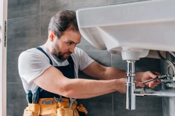 Moviveret håndværker, der arbejdre med en badeværelsesvask