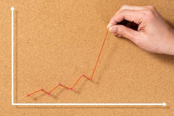 En hånd, der styrer en tråd, der illustrerer en graf, der går op op op